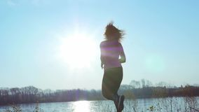 Sportive girl jogging along the river bank during sunrise or sunset. Healthy lifestyle concept of athletic woman goes in. Sportive girl jogging along the river stock footage