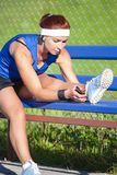 Sportive Girl in Outdoor Outfit Having a Break with Smartphone Outside While Listening to Music. Sport Ideas. Portrait of Concentrated Caucasian Sportswoman in stock image