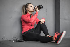 Sportive girl relaxing in gym. Attractive sportive girl sits on the floor in the gym next to the gray wall. She drinks from the black cup in the right hand and Royalty Free Stock Image