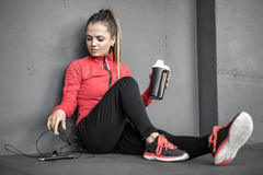 Sportive girl relaxing in gym. Cute sportive girl with closed eyes sits on the floor in the gym next to the gray wall. She holds a cup in the left hand and a Stock Images