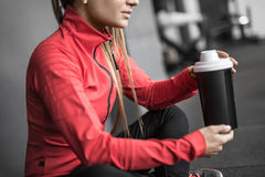 Sportive girl relaxing in gym. Peaceful sportive girl sits on the floor in the gym next to the gray wall. She holds a black cup in the hands. Woman wears black Royalty Free Stock Image