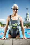 Sportive girl in the swim pool. Athletic girl in the swimming pool outdoors. She wears a multi-colored swimsuit, a white swim cap and swim glasses. Woman looks stock photography