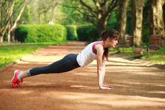 Sportive girl working out doing push ups press exercise Stock Photo