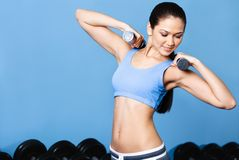 Sportive girl works out with dumbbells royalty free stock photo