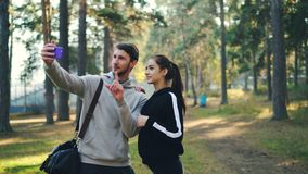 Sportive girlfriend and boyfriend are making online video call using smartphone standing in park together looking at. Sportive girlfriend and boyfriend are stock video