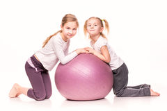 Sportive girls on a fit ball isolated over white. Sportive cute little girls on a fit ball isolated over white Stock Images