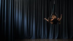 Sportive girls performs a trick in the aerial hoop. Two beautiful gymnasts performs trick at the aerial hoop. Young women makes some graceful elements in the air stock footage