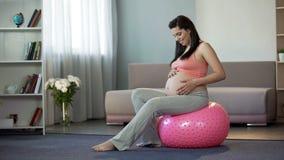 Sportive gravid damsammanträde på konditionbollen som lyssnar till hennes slå för babys arkivbilder