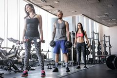 Two beautiful girls with their coach doing functional crossfit training with dumbbells in the gym. Sportive group doing functional crossfit training with royalty free stock photo