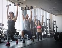 Two beautiful girls with their coach doing functional crossfit training with dumbbells in the gym. stock photos