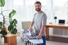 Sportive guy ironing diligently shirt on ironing board Stock Photo