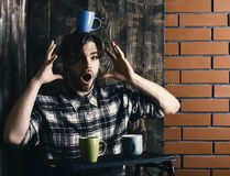 Handsome guy holding cups on brick and wooden wall background. Sportive handsome bearded guy in black and white checkered shirt surprise face holding tray with Royalty Free Stock Photos