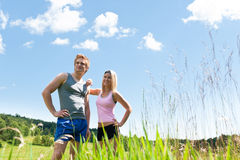 Sportive happy couple in meadows sunny day Royalty Free Stock Photos