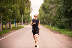 Sportive jogga för ung man som är utomhus- Arkivbild