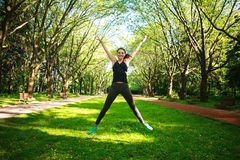 Sportive junge Eignungsfrau, die in Sommerpark springt stockfoto