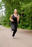 Sportive junge Frau, die über eine forrest Straße läuft Stockbilder