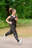 Sportive junge Frau, die über eine forrest Straße läuft Stockfoto