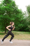 Sportive junge Frau, die über eine forrest Straße läuft Stockfotos