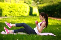 Sportive junge Frau, die mit den Dummköpfen, Eignung tuend ausdehnt Lizenzfreie Stockbilder