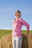 Sportive junge Frau entspannen sich durch Ballensonnenuntergang Lizenzfreies Stockfoto