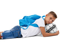A sportive kid with a bright satchel lying on the ground. A little footballer isolated on a white background. A little boy with a head on a ball. A cute tired Stock Photos