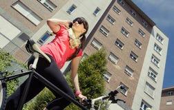 Sportive kobieta dzwoni telefonem z fixie rowerem fotografia stock