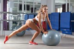 Sportive kvinna med en boll i idrottshallen Royaltyfri Foto