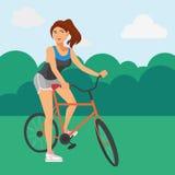 Sportive kvinna som rider en cykel i parkera arkivfoton