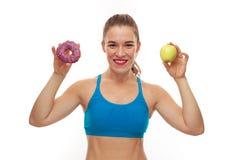 Sportive kvinna som väljer mellan munken och äpplet arkivfoton