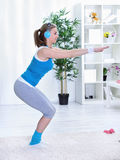 Sportive lady doing squatting at home Stock Photos