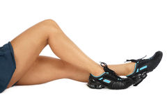 Sportive legs. Slim sportive legs of tanned woman in sneakers sitting on white background Royalty Free Stock Image