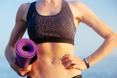 Sportive leisure woman with perfect body holding yoga mat. Health life concept. Stock Image