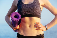 Sportive leisure woman with perfect body holding yoga mat. Health life concept. Sportive leisure woman with perfect body holding yoga mat with fitness bracelet Stock Photo
