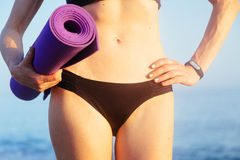 Sportive leisure woman with perfect body holding yoga mat. Health life concept. Royalty Free Stock Images