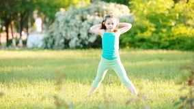 Sportive little girl doing a cartwheel on the meadow in the summer park. stock video