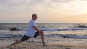 Sportive mężczyzna rozciągania noga na seashore z fala przy wschodem słońca zbiory