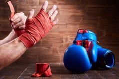 Sportive mężczyzna zawija jego ręki z bandażem i bokserskimi rękawiczkami na drewnianej desce Obraz Royalty Free