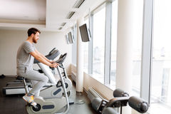 Sportive male exercising on bicycle Royalty Free Stock Images