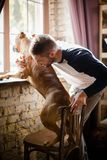 Sportive male and his dog standing by windowsill. Royalty Free Stock Image