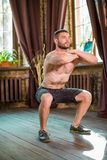 Sportive man doing squats at home. Doing workout at home Stock Images