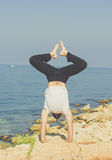 Sportive man is doing yoga on the beach Royalty Free Stock Images