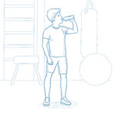 Sportive man drinking water in the gym. Royalty Free Stock Photography
