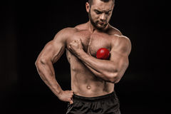 Sportive man holding apple on arm isolated on black. Shirtless sportive man holding apple on arm isolated on black Stock Photos