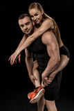 Sportive man looking at camera and piggybacking smiling woman. Sportive men looking at camera and piggybacking smiling women isolated on black Stock Photography