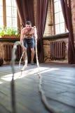 Sportive man med den nakna torson som arbetar med rep för att utbilda armmuscules royaltyfri bild