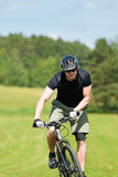 Sportive man mountain biking uphill sunny meadows Stock Photo