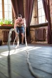 Sportive man with naked torso working with ropes to train arm muscules. Sport at home concept, male doing sport exercises Royalty Free Stock Image