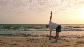 Sportive man practicing yoga in extended triangle pose on seashore. Sportive man practicing yoga in extended triangle pose utthita trikonasana on seashore at stock video footage