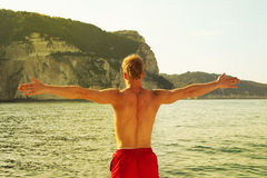 Sportive man on the sea with outstretched arms. Pure liberty. Royalty Free Stock Photography