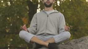 Sportive man sitting in lotus position on rock top, meditation and relax, hobby stock video footage